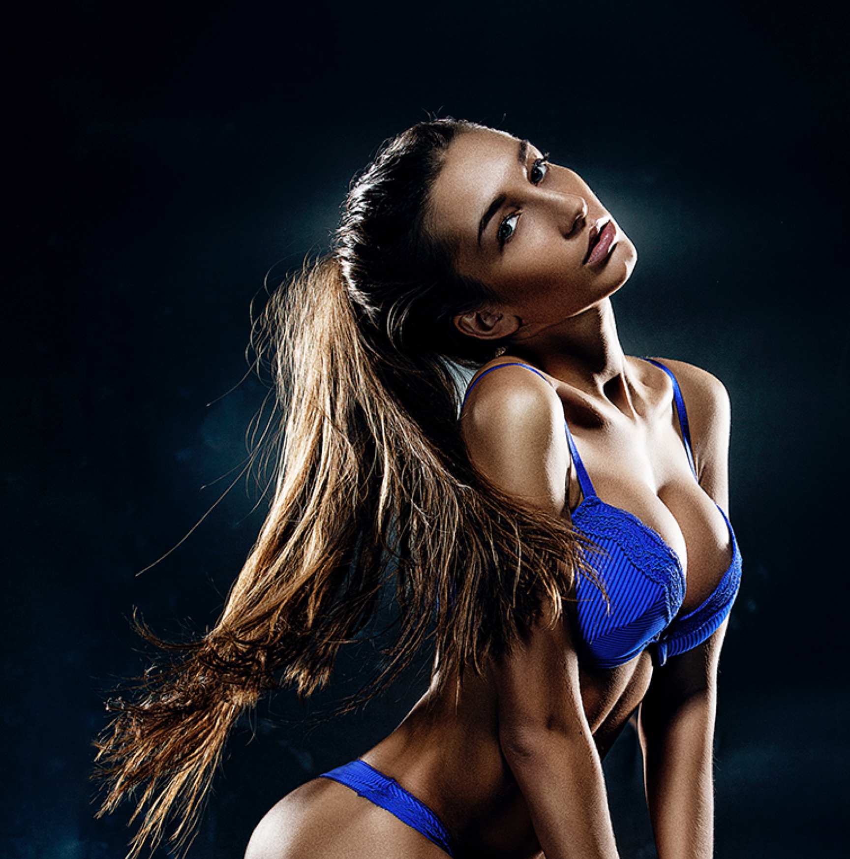 Young brunette model with long hair up in a pony tail and large breasts in a cobalt blue bra